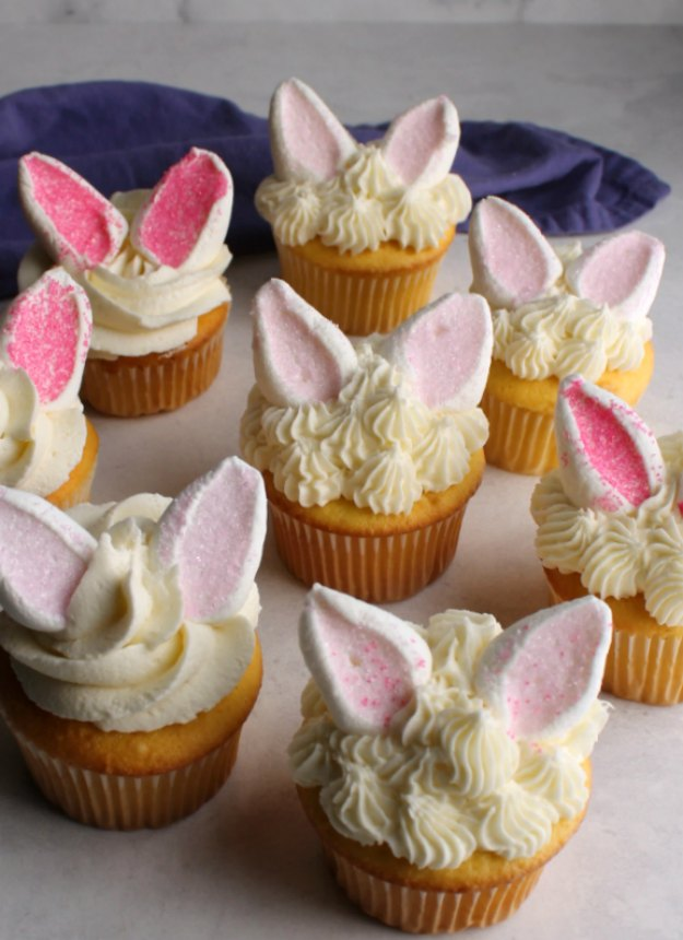 collection of bunny cupcakes with fluffy white frosting and marshmallow ears with pink sugar inside.