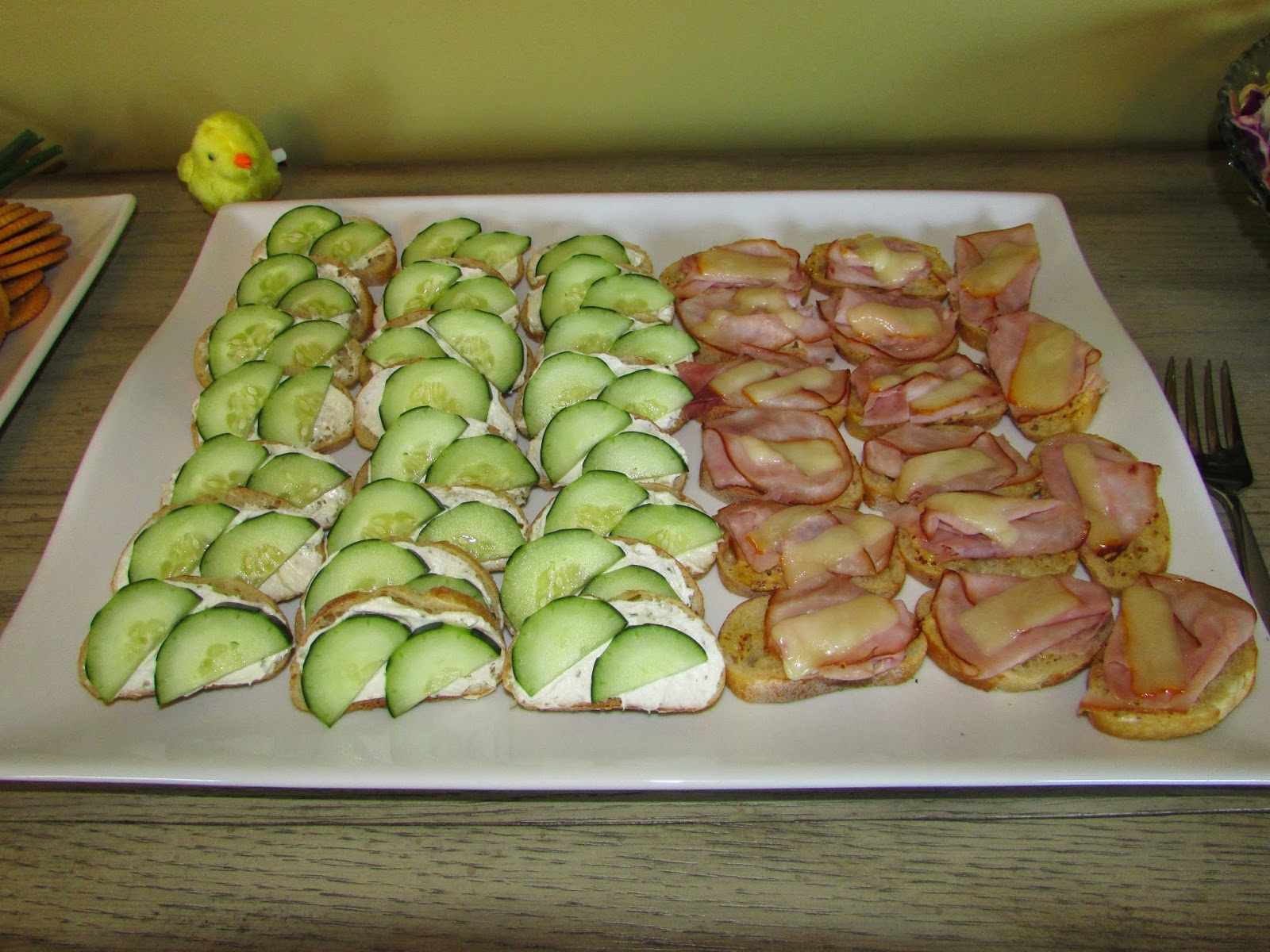 Tray of open faced cucumber sandwiches and ham and cheese crostini.
