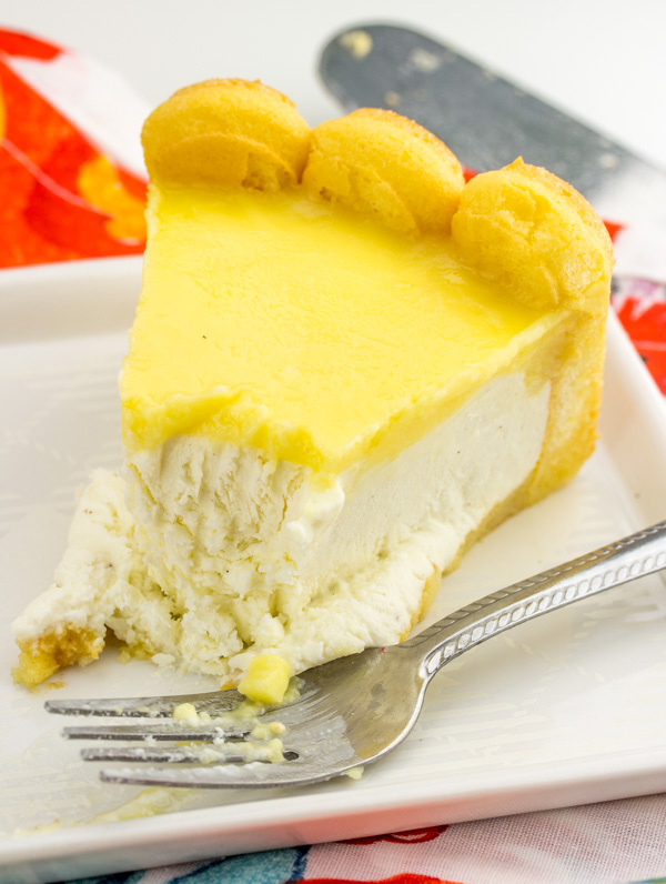 slice of orange topped cheesecake on plate with bite missing from tip