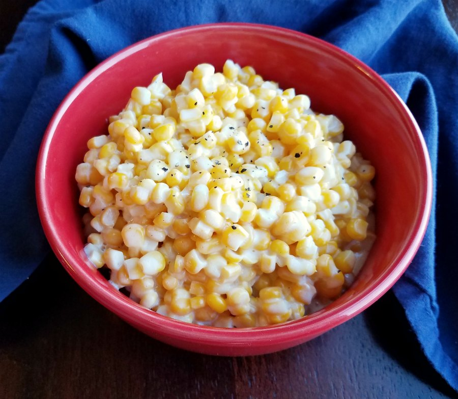 creamy corn in red bowl with sprinkling of black pepper on top