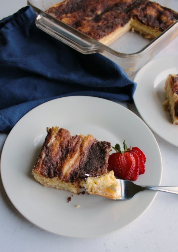 Crescent cheesecake bars topped with cinnamon sugar, with bite on fork showing creamy sweet center.