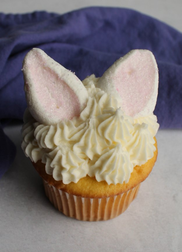 single cupcake with piped dollops of white frosting fur and marshmallow ears.