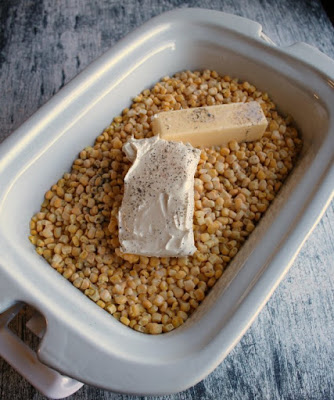 corn, butter and cream cheese in slow cooker ready to cook