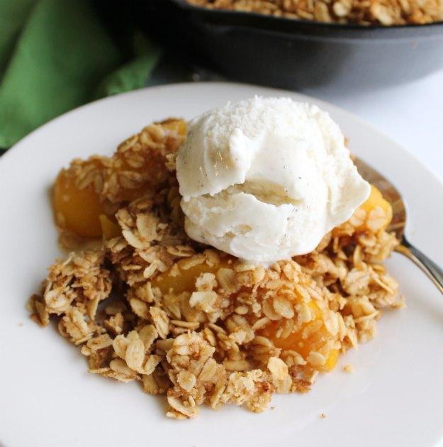 close up of serving of peach crisp with scoop of vanilla ice cream