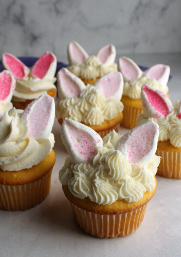 collection of cupcakes with different piping designs for frosting and marshmallow rabbit ears on top, ready for Easter.