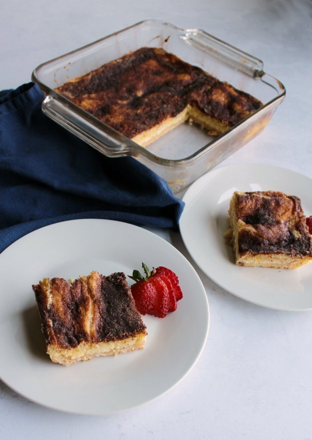two servings of cinnamon crescent cheesecake bars served with pan in background