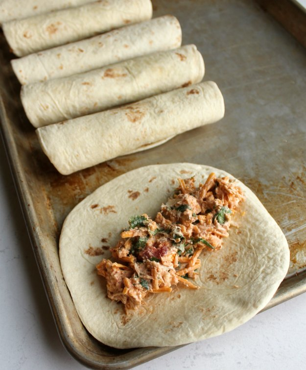 filling on tortilla ready to be rolled up next to taquitos on baking tray.