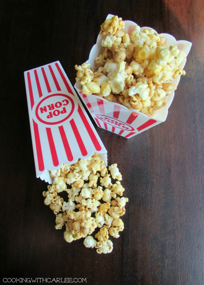 two red and white striped popcorn containers filled with crunchy caramel corn
