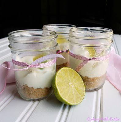 pint jars with cheesecake filling about half way up, ribbon bows and slices of lime