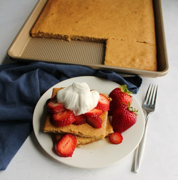 stack of square pancakes topped with strawberry slices and maple whipped cream. Remaining sheet pan pancake in background