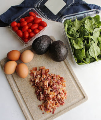 tub of tomatoes, spinach, avocados, eggs and bacon ready to be stirred into pasta salad
