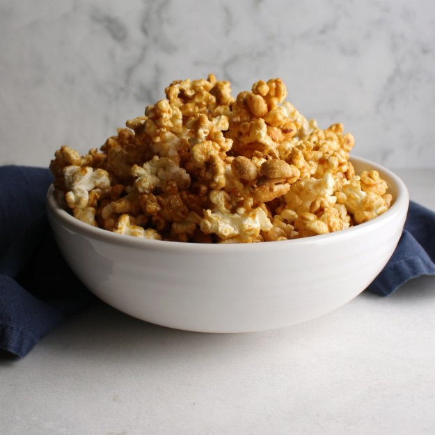 white bowl filled with cracker jack style crunchy caramel corn with lots of peanuts