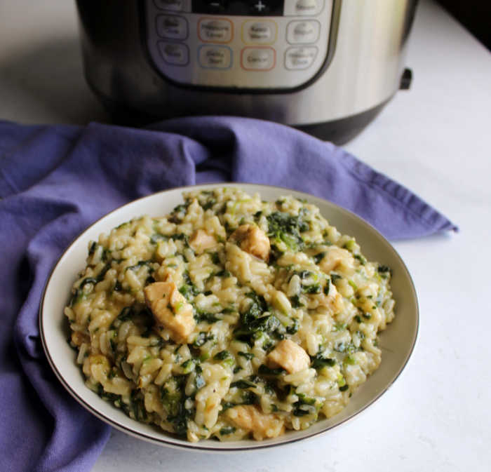 Bowl of spinach and chicken risotto in front of instant pot.