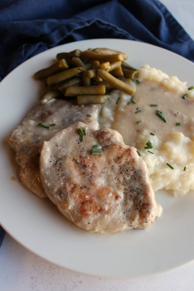 close up of tender pork chops and mushroom soup gravy served with mashed potatoes and green beans.