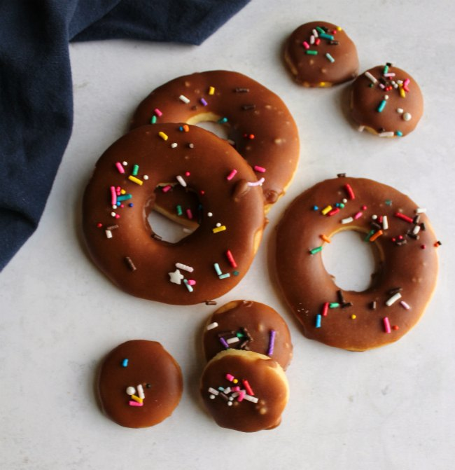 sugar cookies shaped like donuts and donut holes with fudge icing and sprinkles.