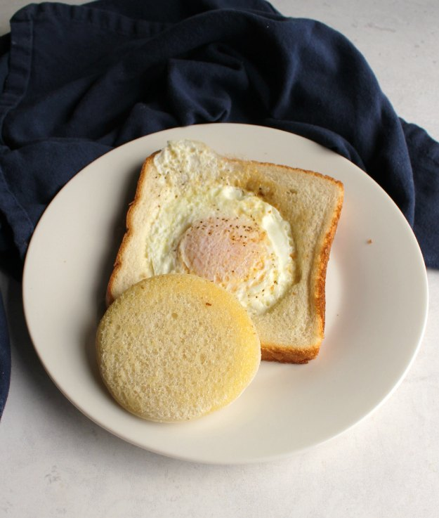 egg in a bread basket on plate with circle of toast over top, ready to eat.