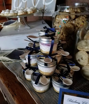 stack of lemon blueberry cheesecake jars with navy ribbon and bamboo spoons