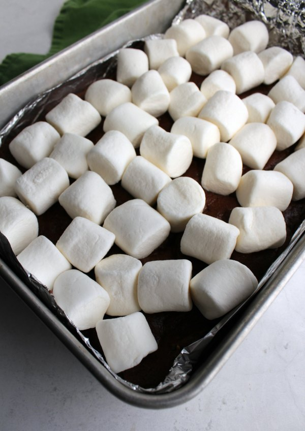 pan of half cooked s'mores bars with bright white marshmallows on top.