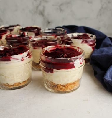 collection of small jars filled with lemon cheesecake mixture and blackberry topping