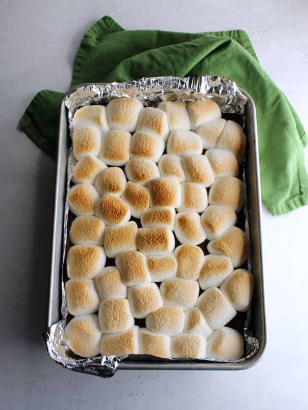 pan of s'mores bars fresh from oven with golden brown marshmallows on top