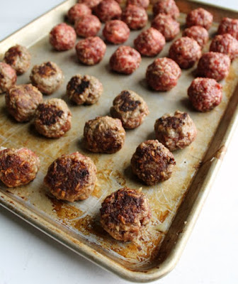 sheet pan filled with meatballs, half browned half raw