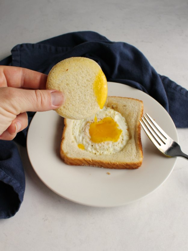 toast with an egg in the middle of it and runny yolk in the center