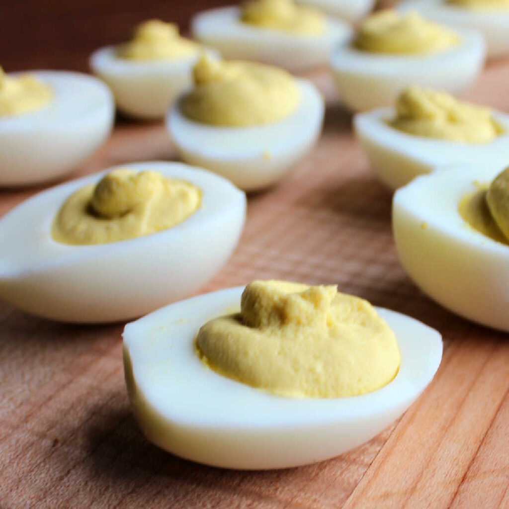 close up of deviled eggs on wood serving board.