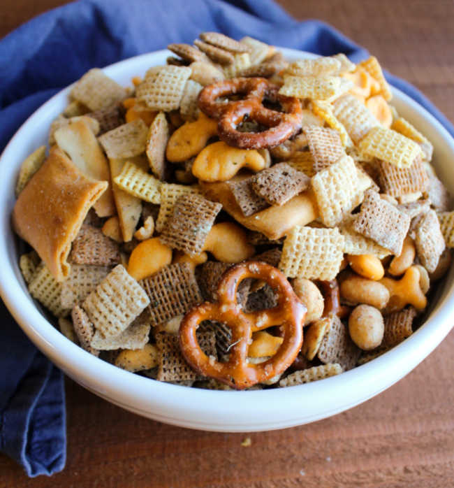 close up bowl of snack mix with pita chips, chex cereal, peanuts, pretzels, fish crackers all coated in dill and ranch seasoning
