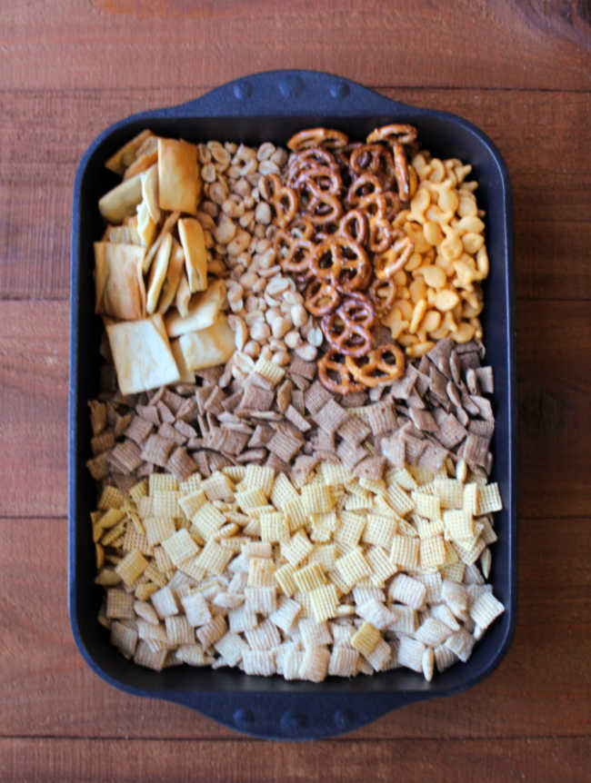 large roasting pan filled with cereal, pretzels, peanuts and more.