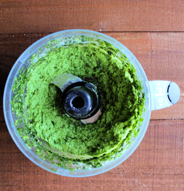 food processor bowl with thick paste of garlic scapes, spinach, Parmesan, butter and oil.