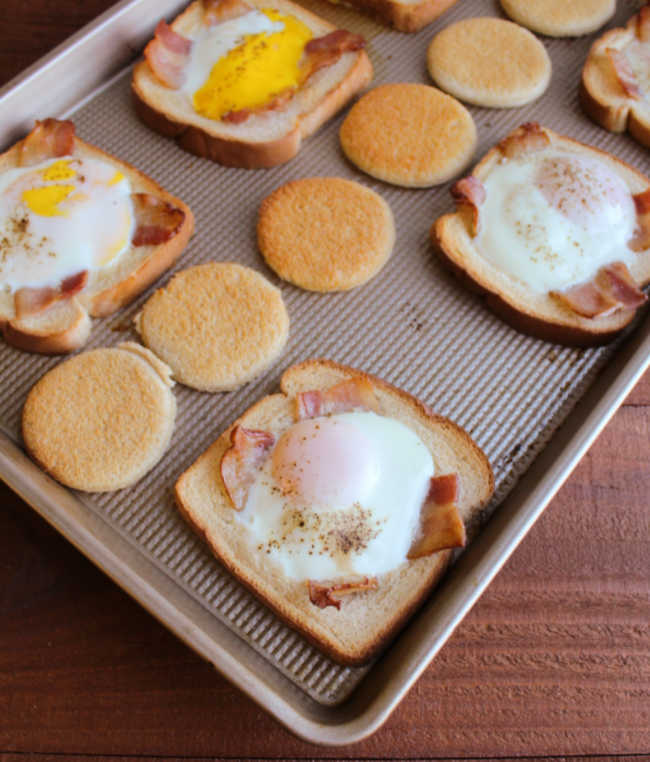 sheet pan with toast circles and eggs in a hole with bacon