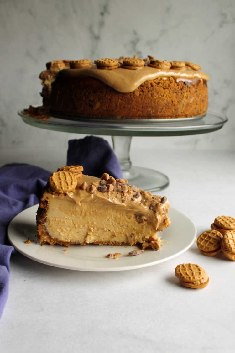 slice of peanut butter cheesecake in front of cake stand holding remaining dessert
