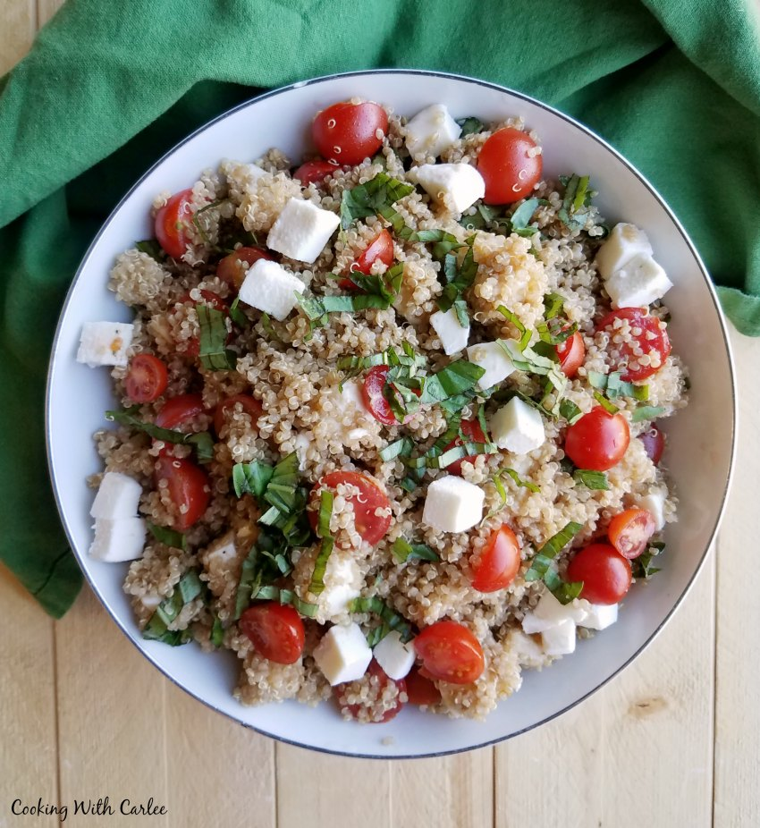 bowl of quinoa salad with tomatoes basil and mozzarella pearls