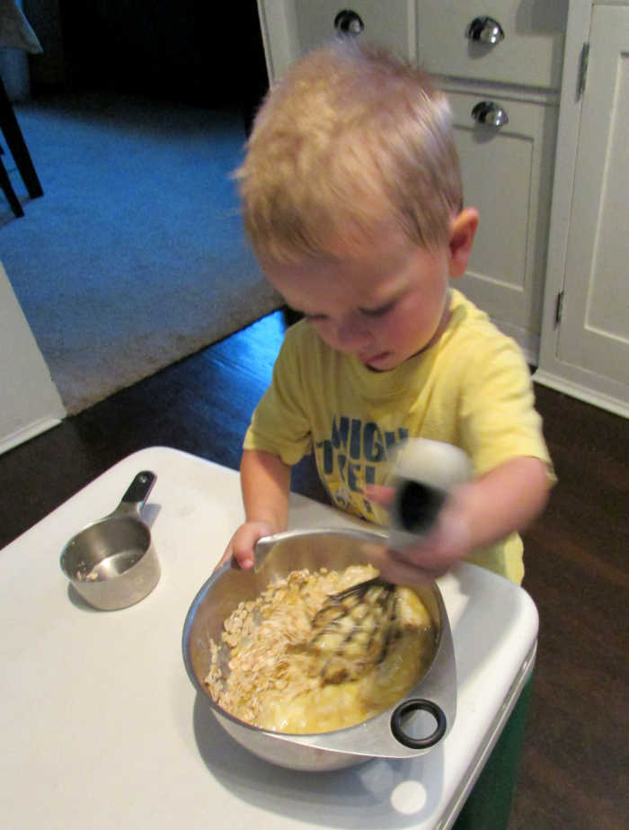 Young kid stirring mixing bowl filled with peach muffin batter.