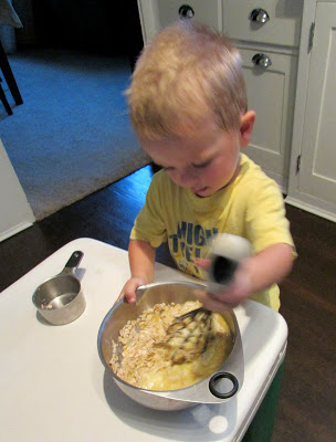 little guy mixing up a bowl of muffin batter