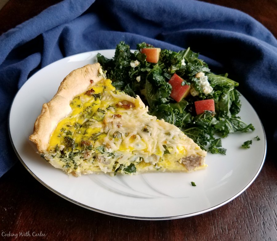 plate with slice of quiche and helping of kale salad