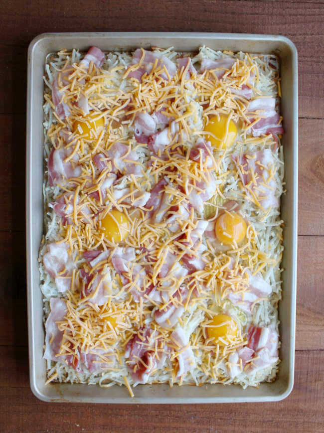 sheet pan filled with hash browns, bacon, eggs and cheese ready to go in oven.