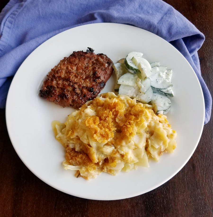 cheesy cabbage casserole served with pork chop and cucumber salad.