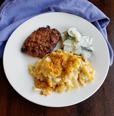 cheesy cabbage casserole served with pork chop and cucumber salad