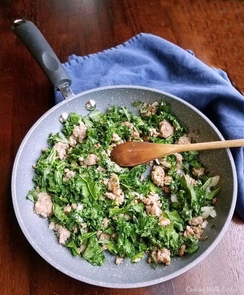 skillet with browned sausage and wilted kale.