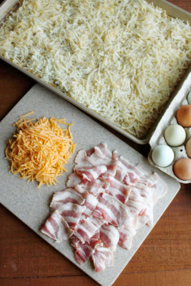 partially cooked hash browns in sheet pan getting ready for eggs, cheese and pieces of bacon.