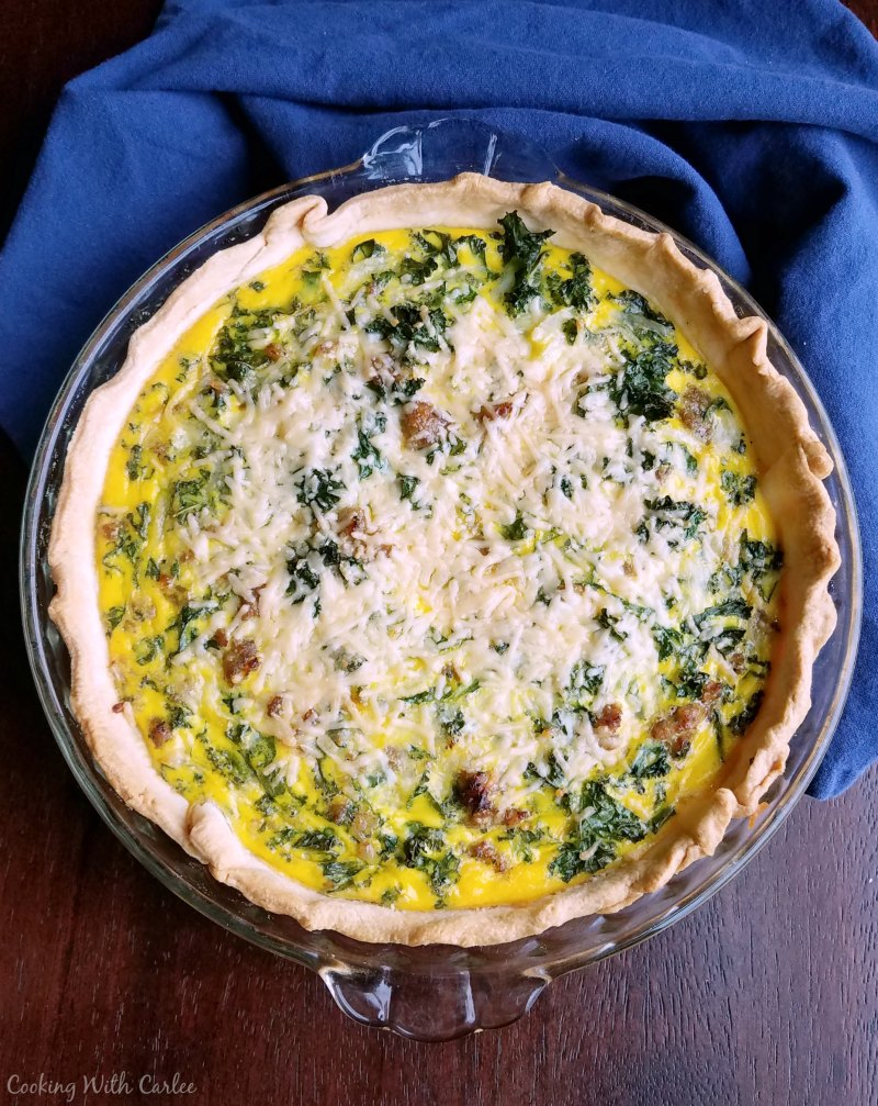 Freshly baked quiche with golden crust, flecks of green kale and plenty of melted cheese on top.