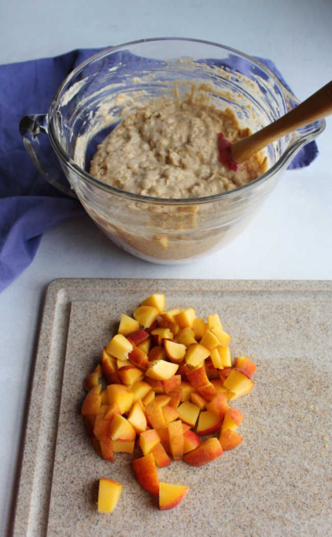 bowl of muffin batter next to cutting board with chopped peach