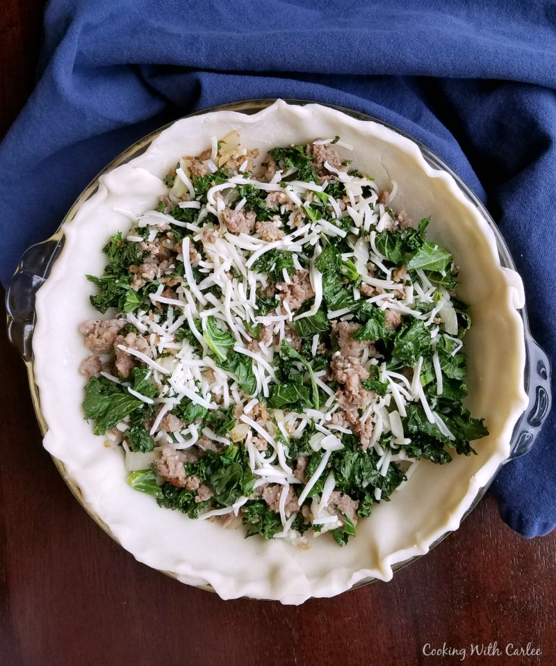Raw pie crust with sausage, kale and cheese in it.