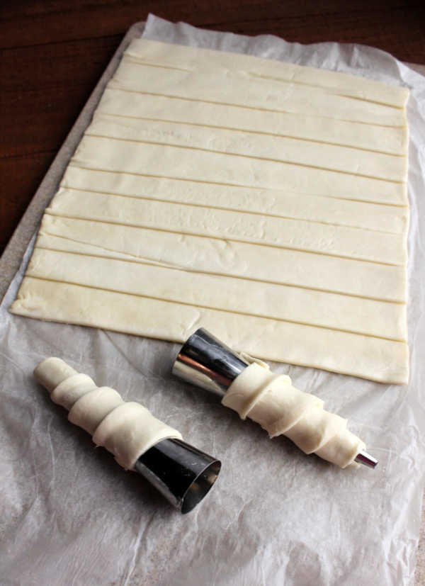 strips of puff pastry with two rolled around metal cone shaped molds