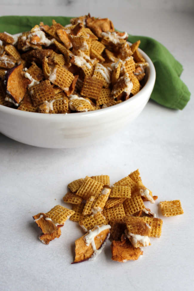 Bowl of apple cinnamon chex mix with some on the counter in front of it showing brown sugar coating and white chocolate drizzle.