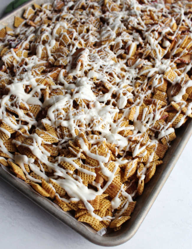 pan full of apple pie snack mix drizzled with white chocolate