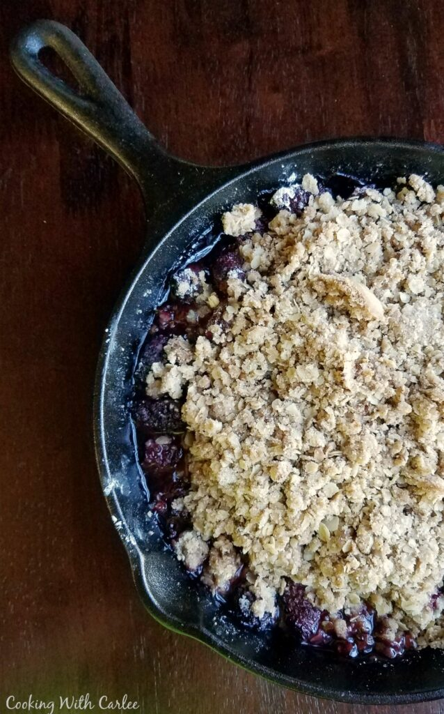 close up of half of a cast iron skillet filled with blackberry crisp.