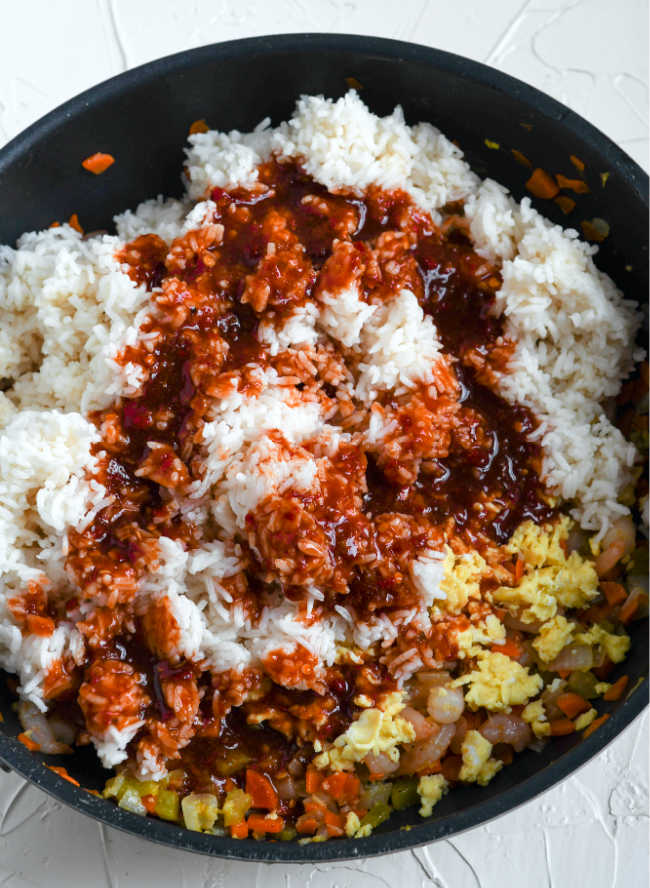 chili sauce and soy sauce mixture poured over rice in skillet