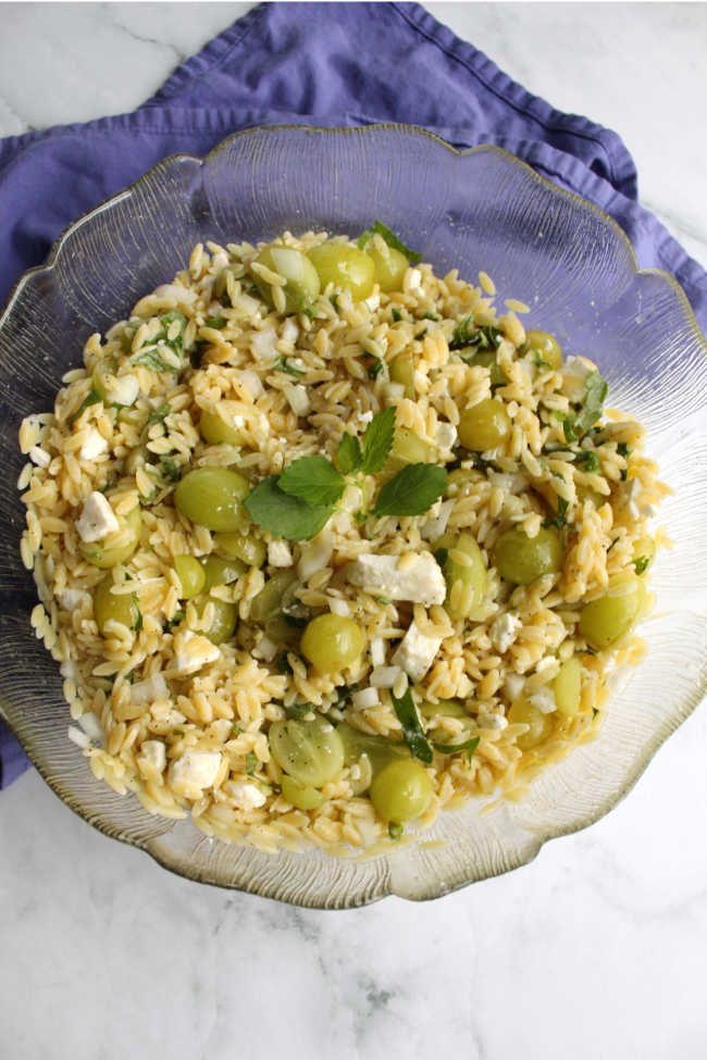 big serving bowl of grape mint and orzo salad.